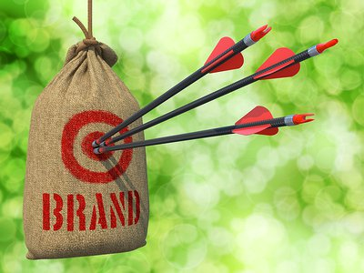 Brand - Three Arrows Hit in Red Target on a Hanging Sack on Green Bokeh Background.